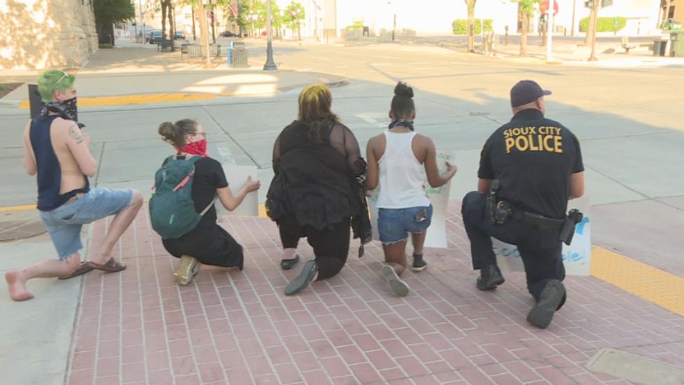 La policía de Sioux City habla con los manifestantes, se arrodillan juntos en protesta por mala conducta